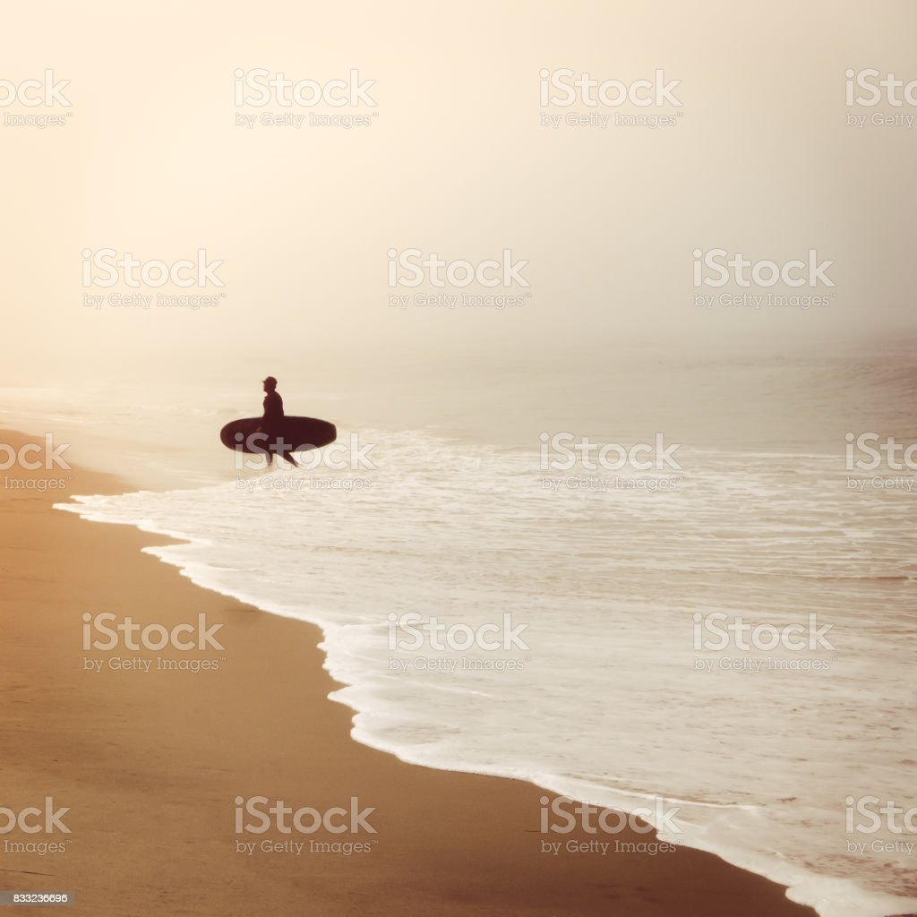 Silhouette of Surfer on Foggy Beach stock photo