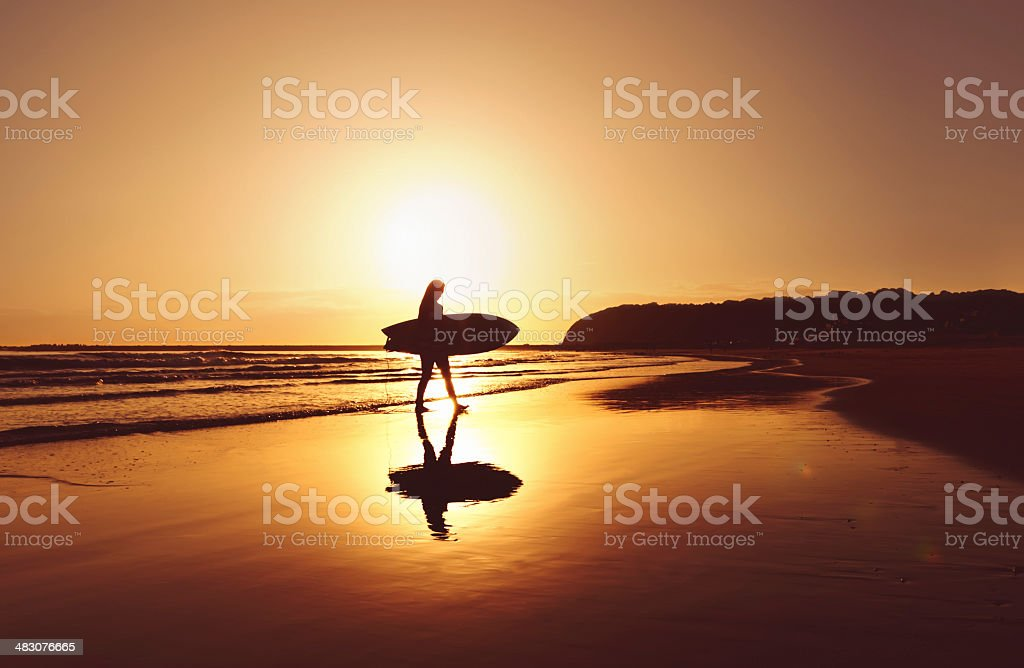 Silhouette of surfer walking off beach with surfboard stock photo
