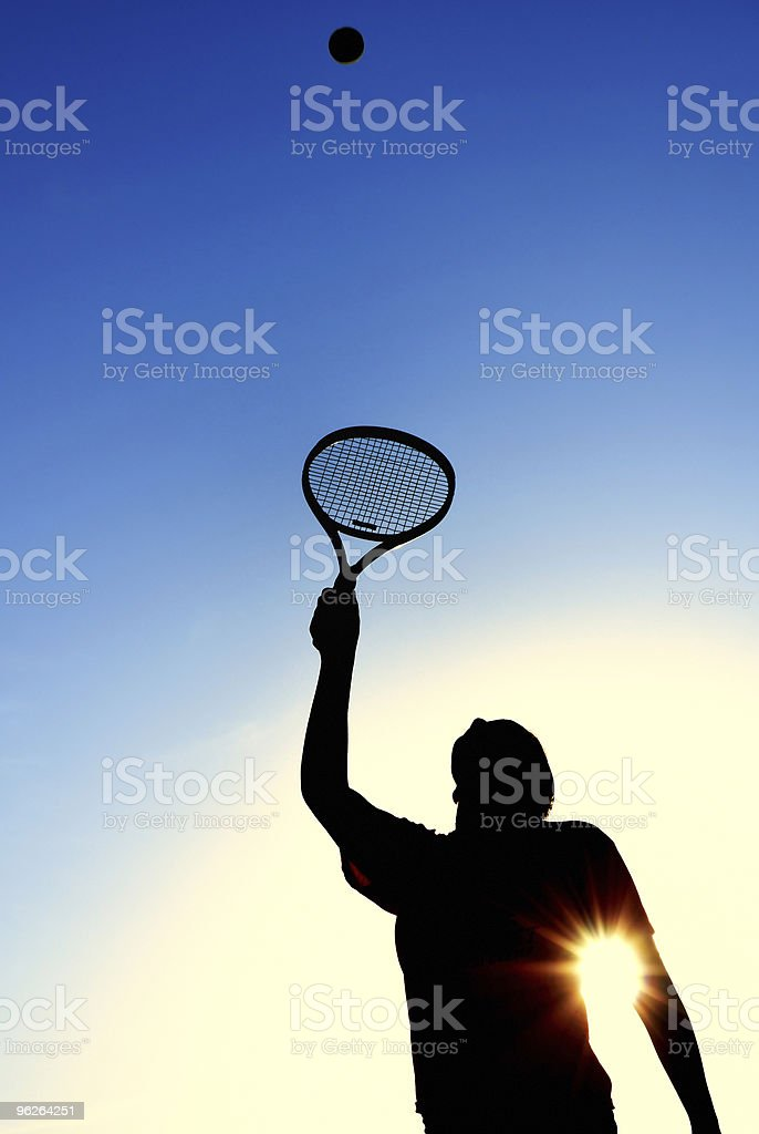 Silhouette of Teen Girl Serving a Tennis Ball royalty-free stock photo