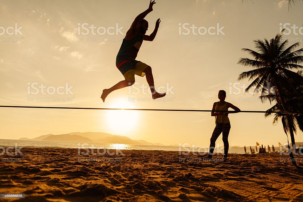 Silhouette of teenager balancing on slackline with spectator stock photo