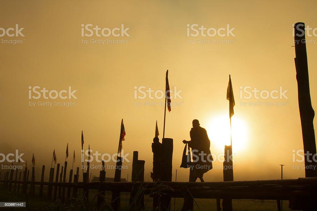 Silhouette of Thai rural Monk walking stock photo