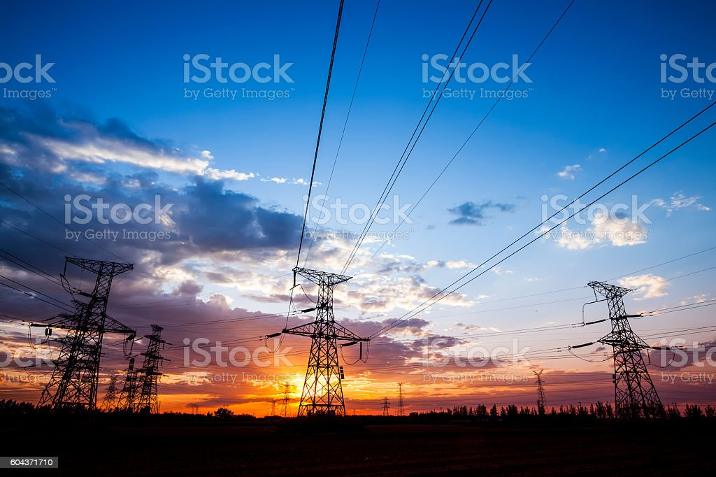 Silhouette of the evening electricity transmission pylon stock photo