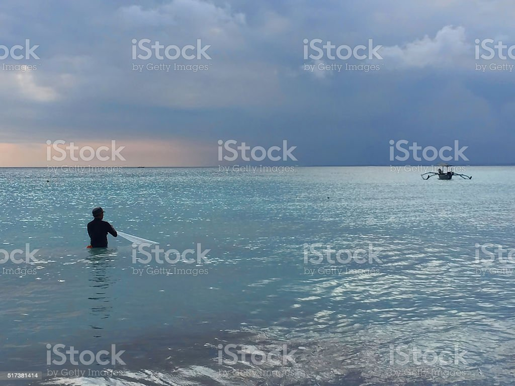Silhouette of the fisherman on a background of blue sea stock photo