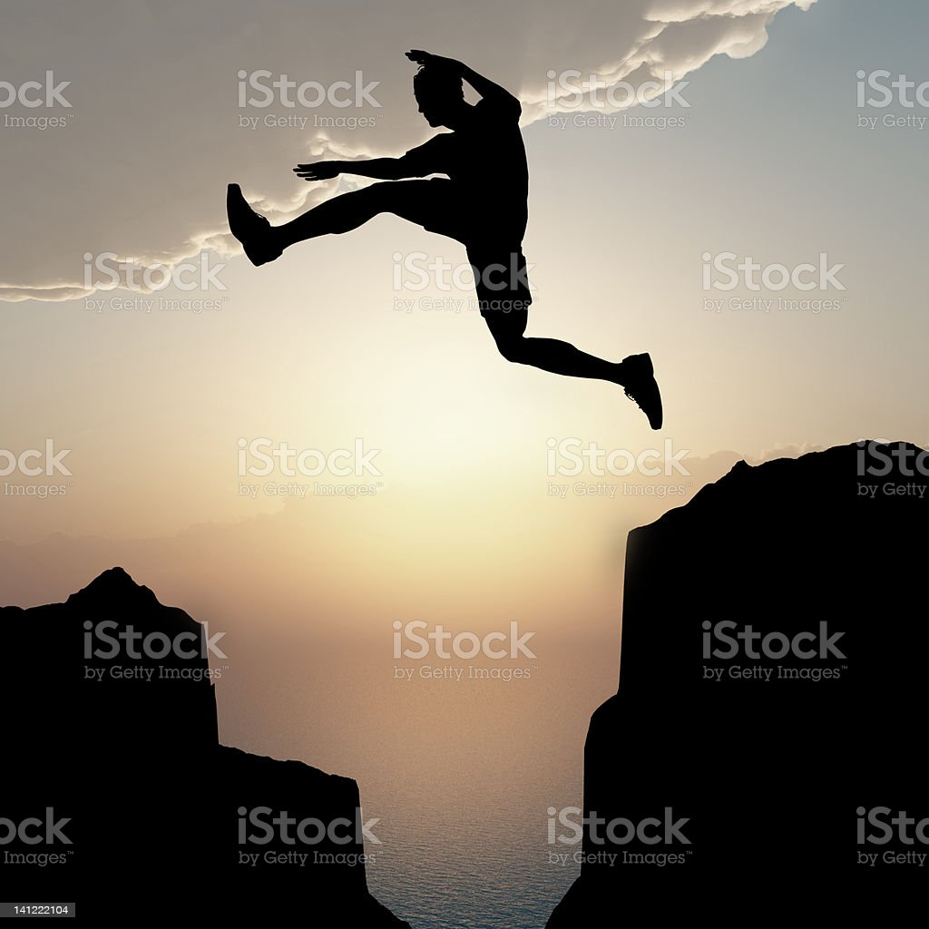 Silhouette of the jumping man from a rock royalty-free stock photo