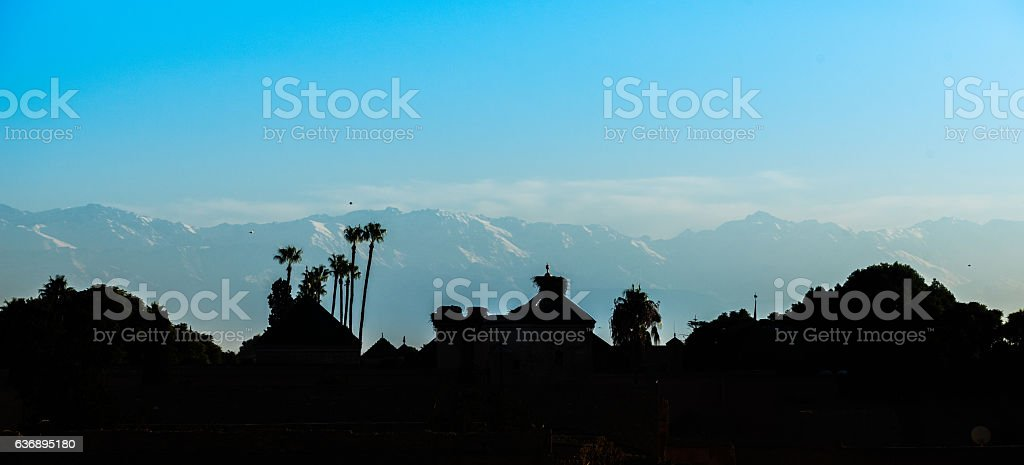 Silhouette of the Merdina of Marrakech with the Atlas mountains stock photo