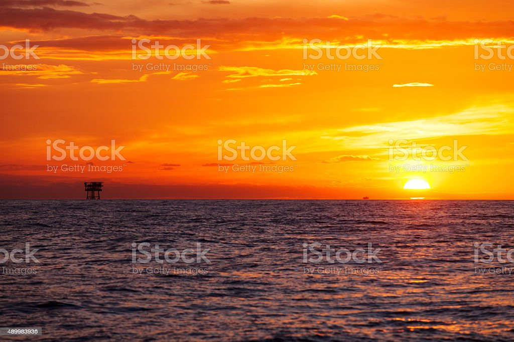 Silhouette of the oil platform during stunning sunset stock photo