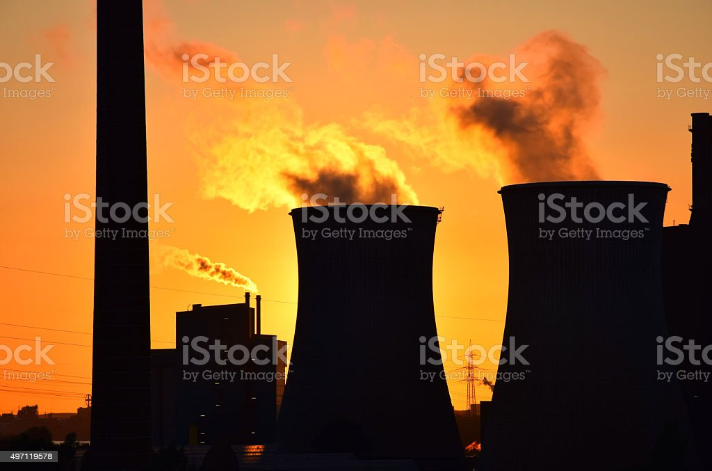 Silhouette of the plant smokestack polluting the air stock photo