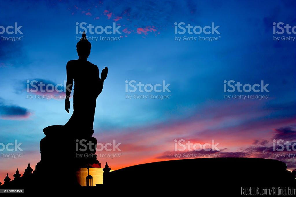 Silhouette Of The Posture Of Walking Buddhist Statue In Twilight stock photo
