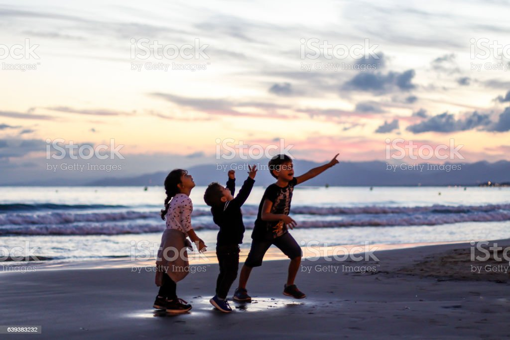 Silhouette of three kids playing on the beach at sunset. stock photo