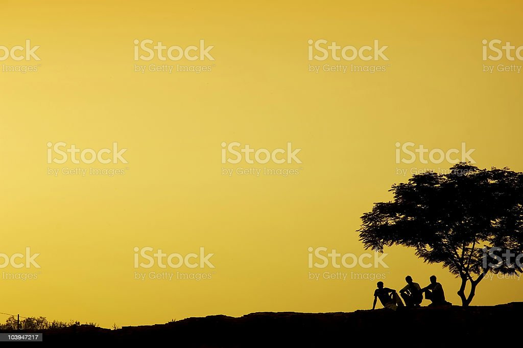 silhouette of three man sitting beside a tree in sunset royalty-free stock photo