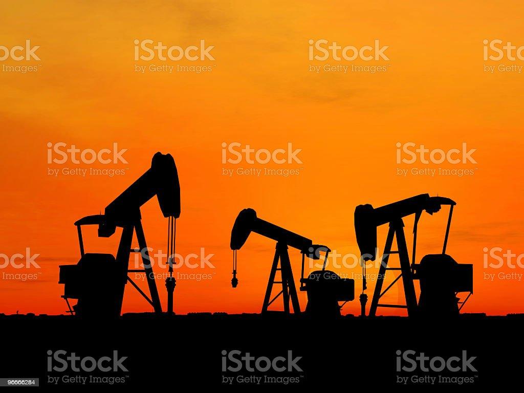 Silhouette of three oil pumps against orange sky stock photo