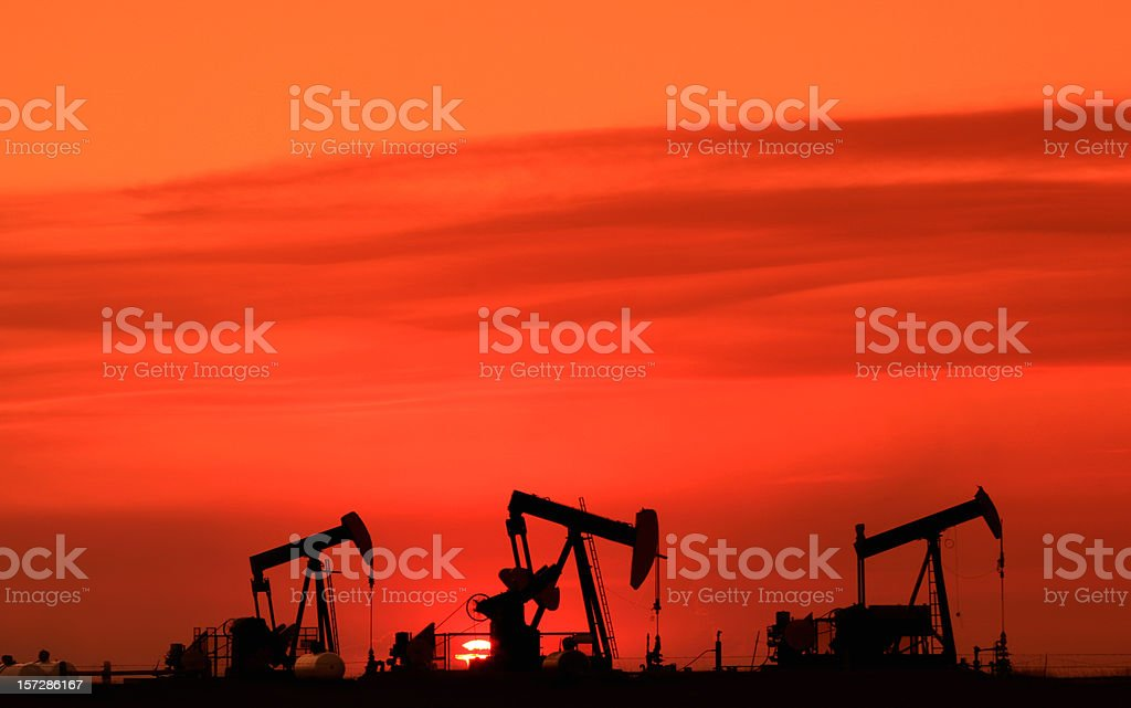 Silhouette of Three Oil Rigs Pumpjacks on the Prairie stock photo