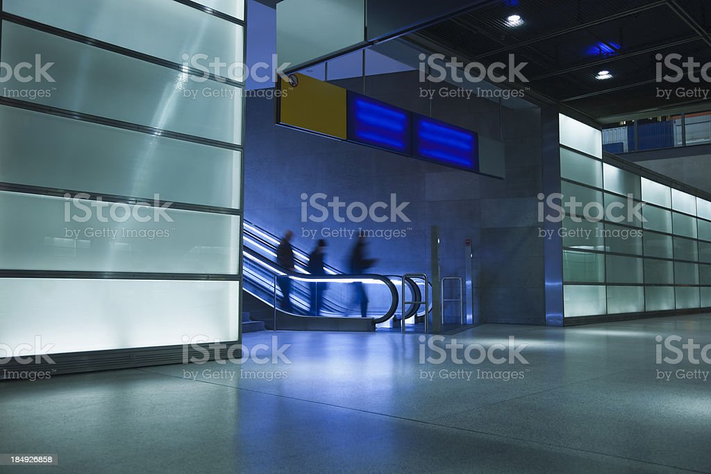 Silhouette of Three Persons on Escalator to Underground Train Station royalty-free stock photo