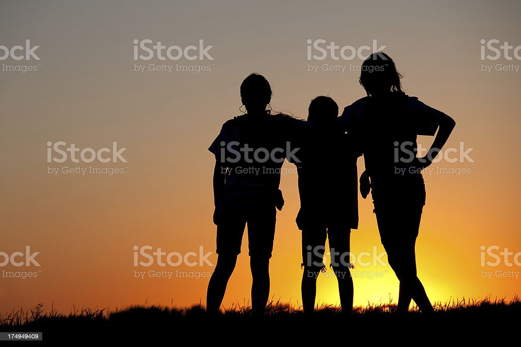 Silhouette of Three Teenagers Bonding at Sunset stock photo