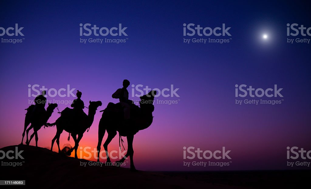 Silhouette of three wise men traveling in the desert stock photo