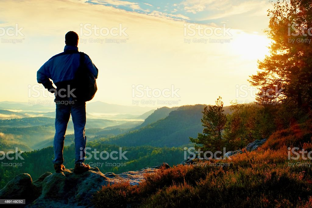 Silhouette of tourist with backpack. Sunny spring daybreak stock photo