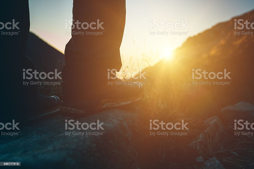 Silhouette of traveler's legs standing on front of the sun stock photo