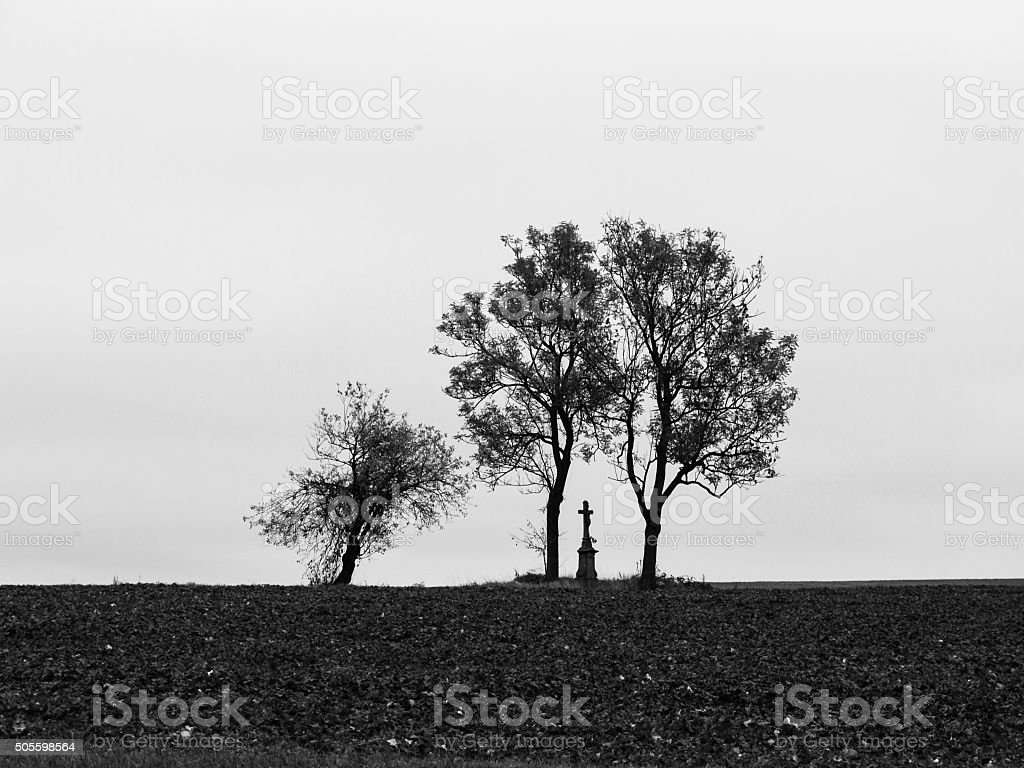 Silhouette of trees and small monument with cross stock photo
