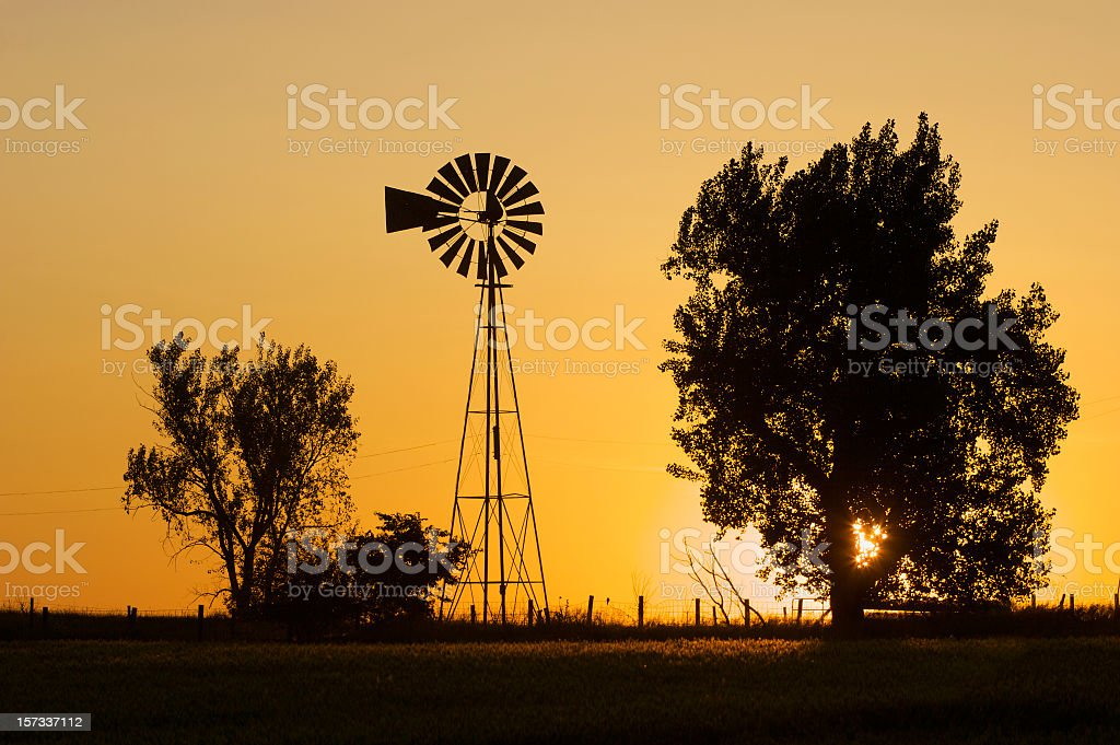 Silhouette of trees and windmill over a Prairie sunrise stock photo