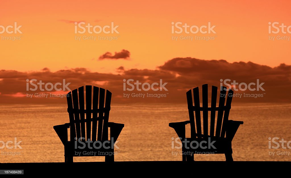 Silhouette of Two Adirondack Chairs on the Beach royalty-free stock photo
