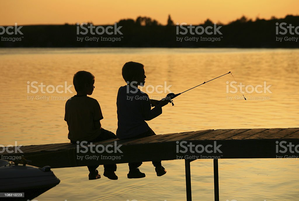 Silhouette of Two Boys Fishing Off A Dock stock photo