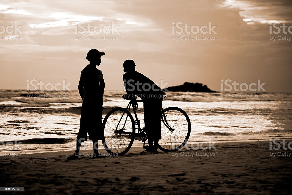 Silhouette of Two Boys on Beach with Bicycle royalty-free stock photo