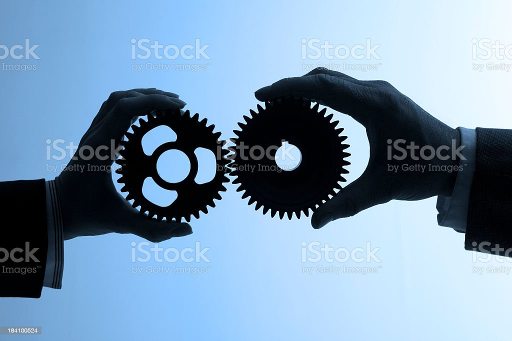 Silhouette of two business people holding gears royalty-free stock photo