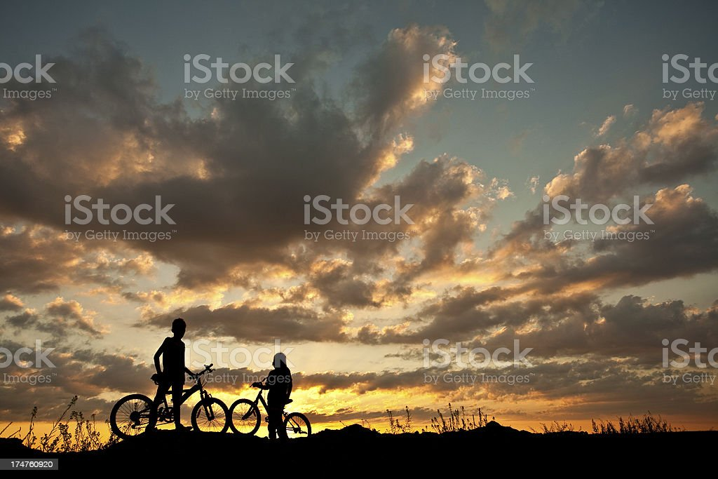 Silhouette of Two Children on Bicycles stock photo