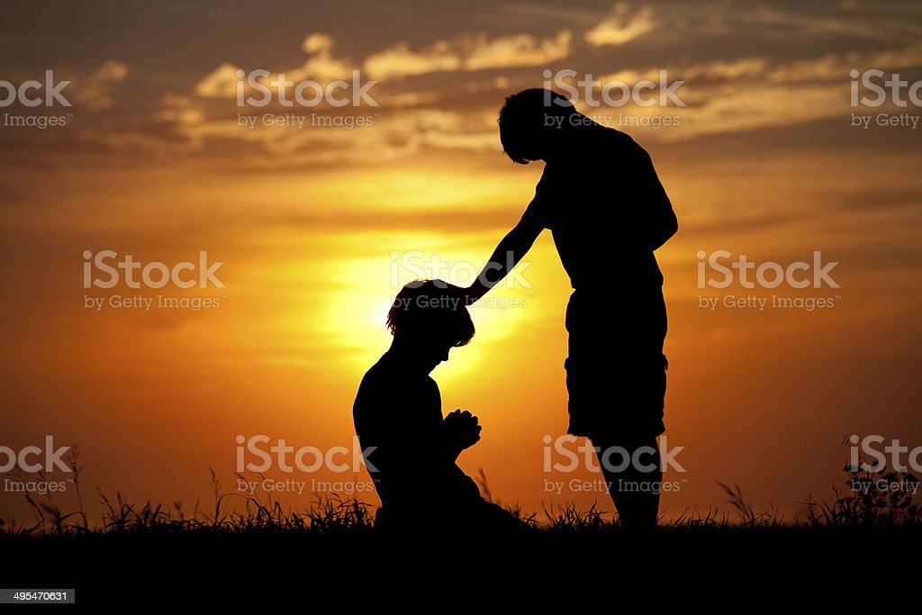 Silhouette of Two Children Praying stock photo