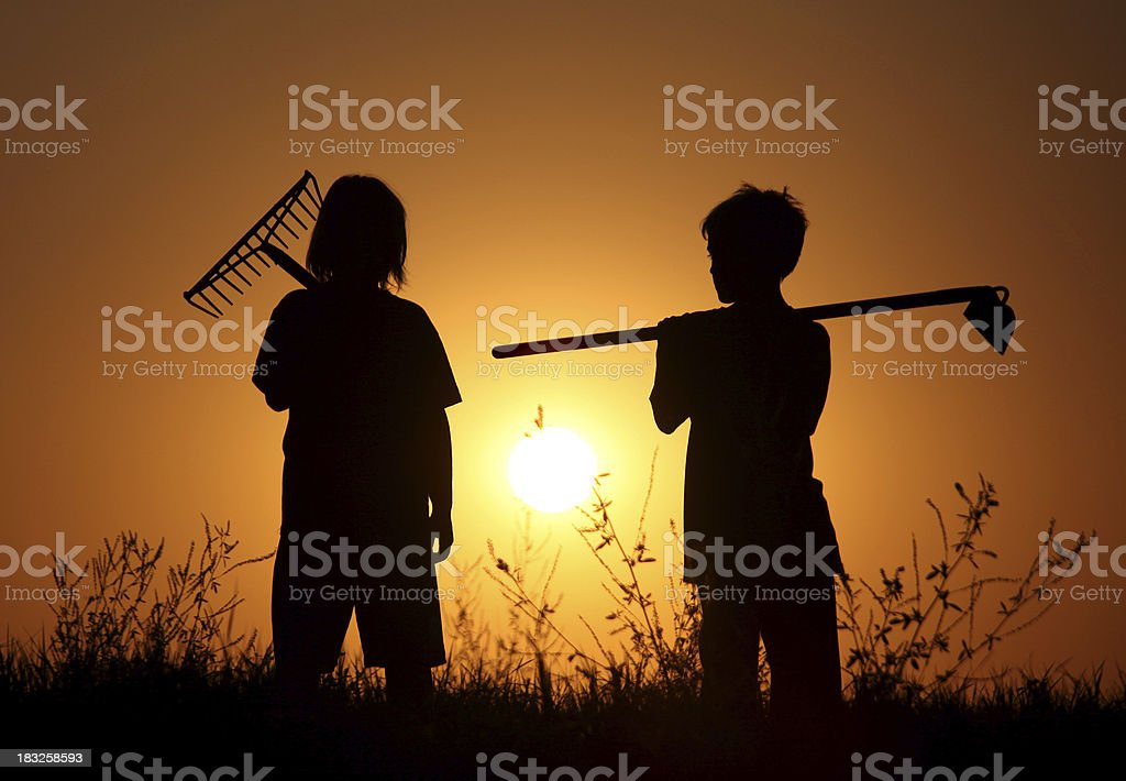 Silhouette of Two Children with Lawn Tools stock photo