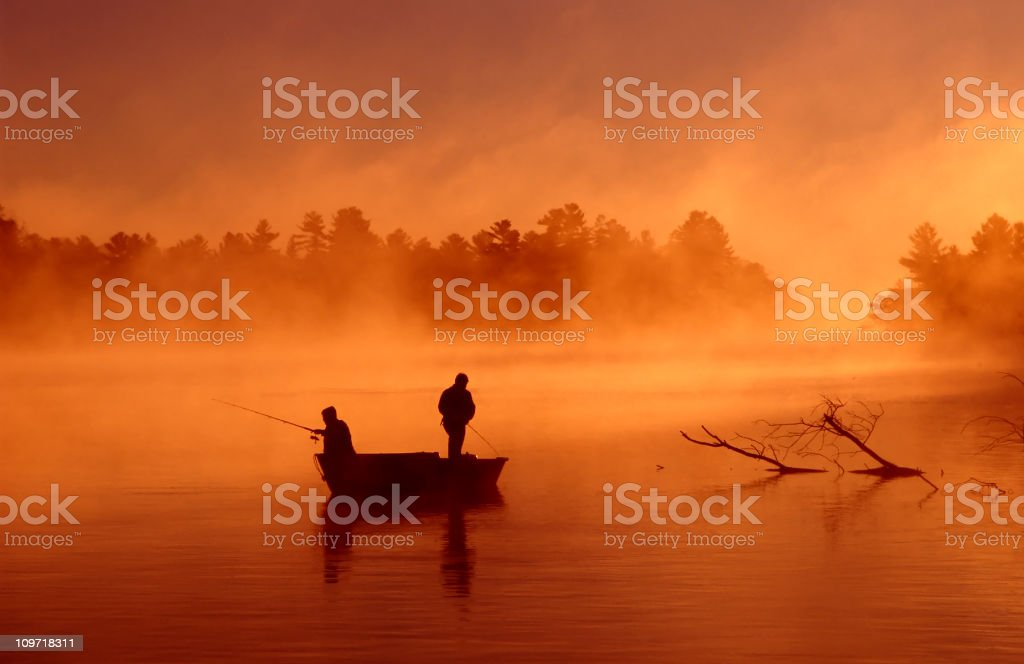 Silhouette of two fishermen on boat on a misty river stock photo
