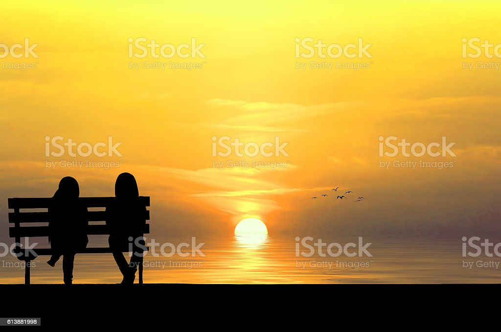 Silhouette of two friends sitting on wood bench near beach stock photo