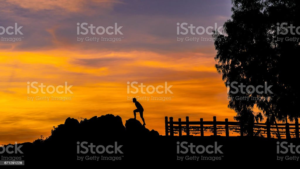silhouette of two happy people in sunset stock photo
