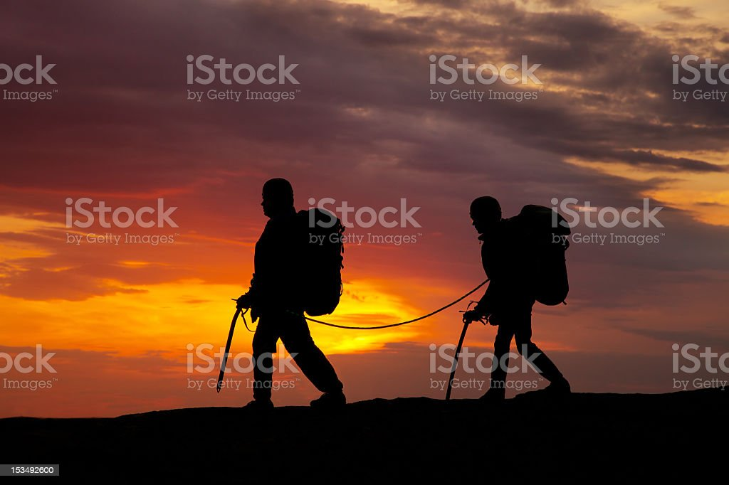 Silhouette of two hikers walking in the sunset royalty-free stock photo