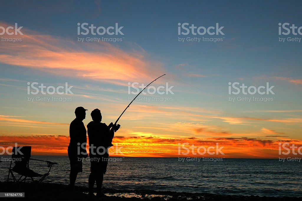 A silhouette of two men fishing at sunset stock photo