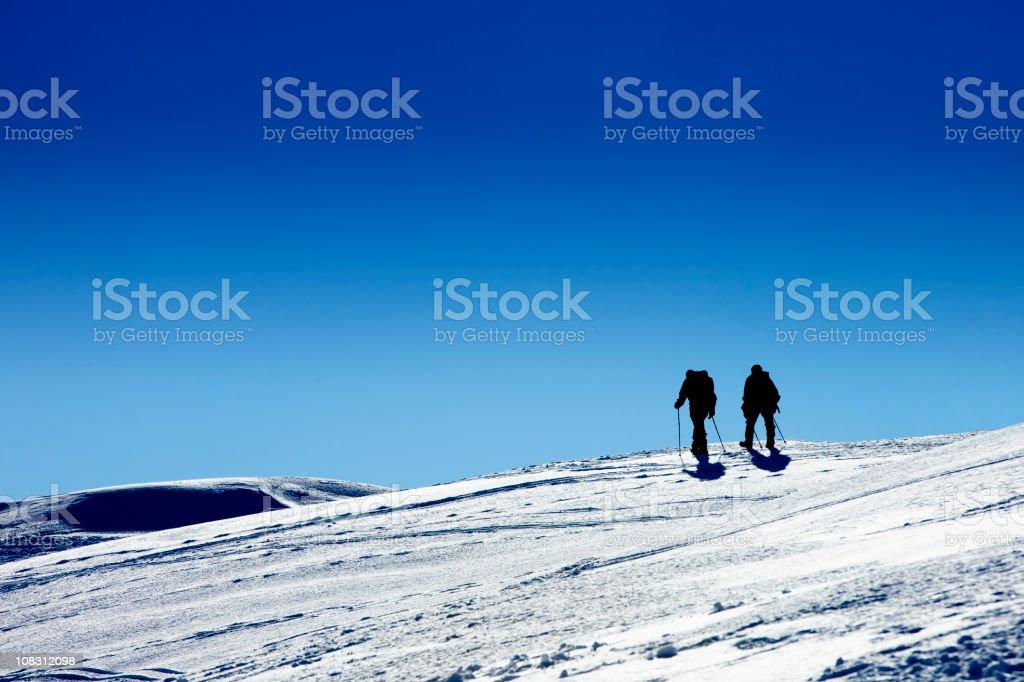 Silhouette of two men on trekking royalty-free stock photo