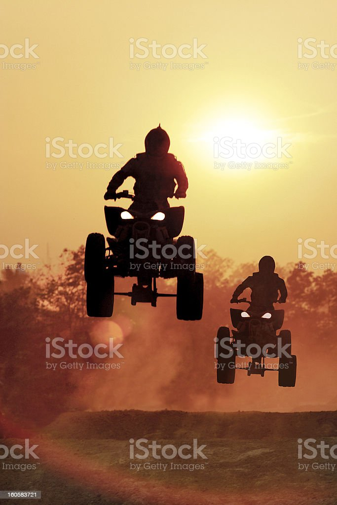 Silhouette of two people doing an ATV jump on a dirt track stock photo