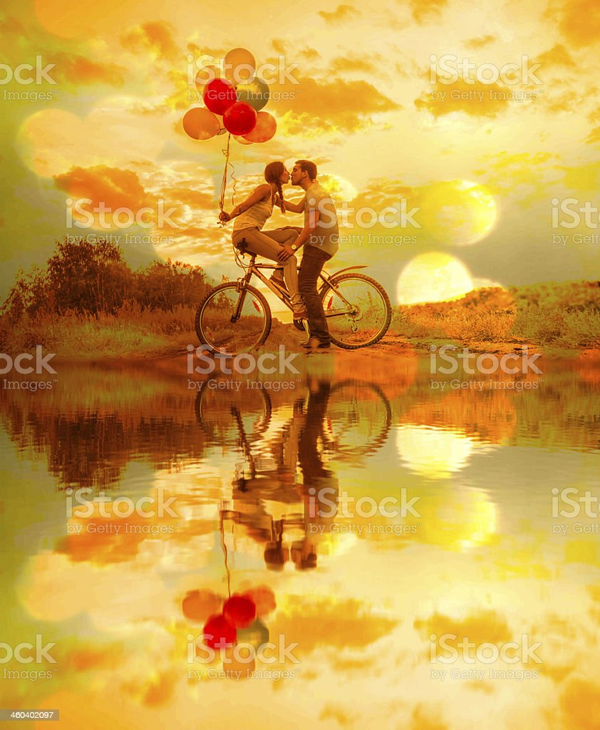 Silhouette of two people Young couple sitting  one bicycle stock photo