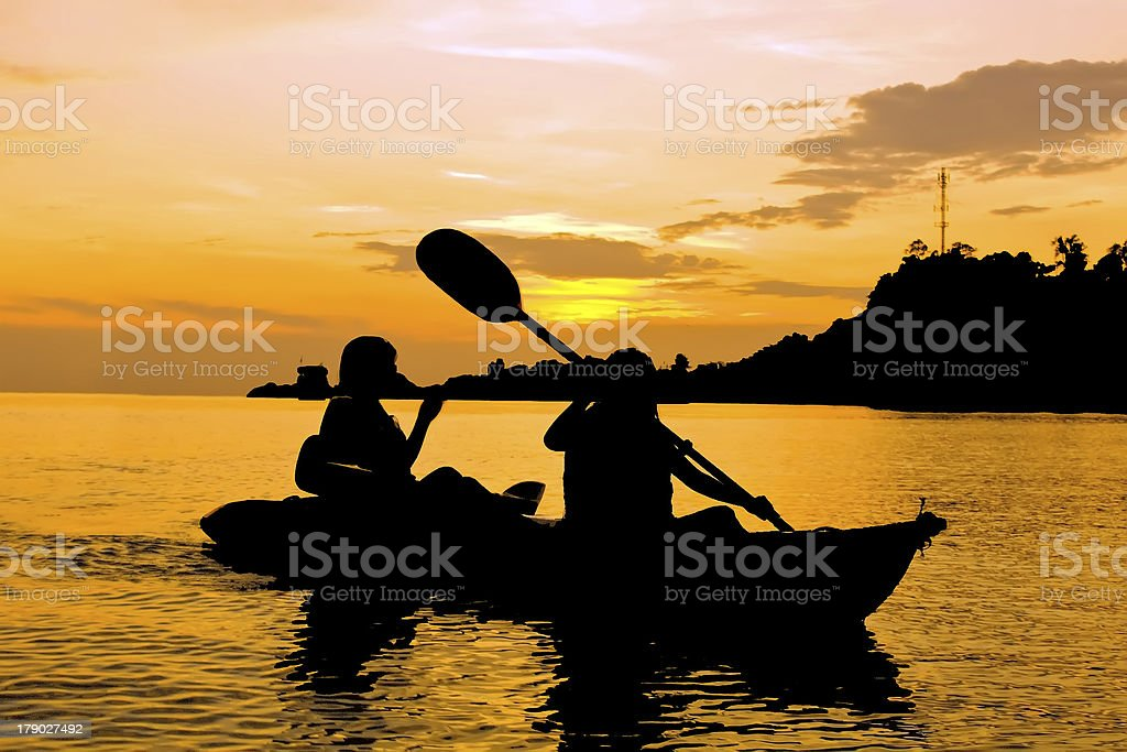 Silhouette of Two person kayaking in the sea stock photo