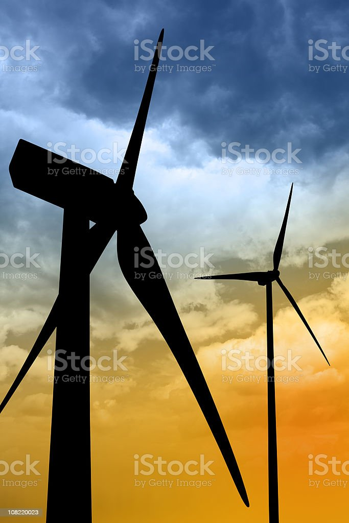 Silhouette of Two Wind Turbines on Colorful Sky royalty-free stock photo