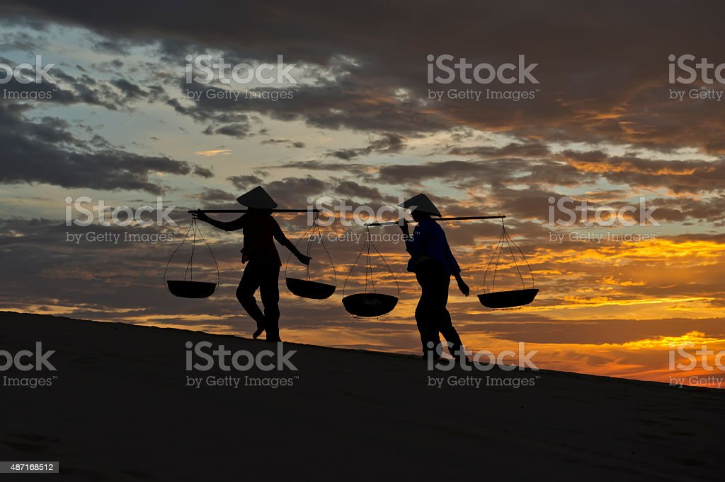 Silhouette of Two Women Carrying Baskets stock photo