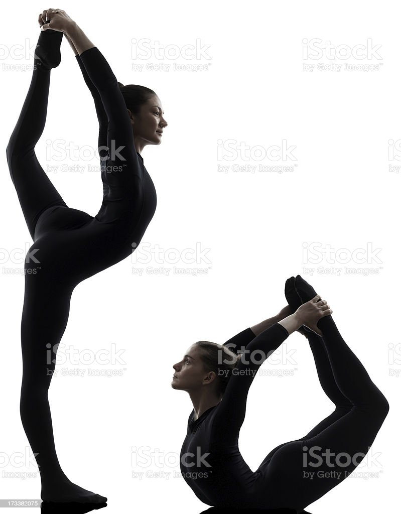 Silhouette of two women in black doing gymnastics stock photo