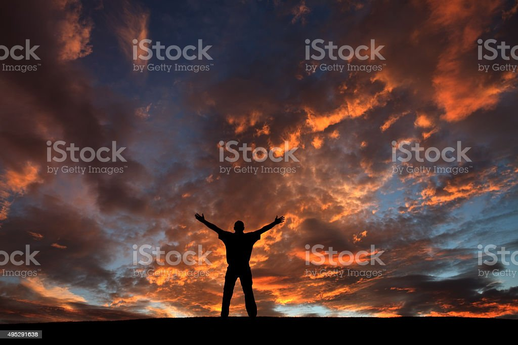 Silhouette of Unrecognizable Male in Praise and Worship stock photo