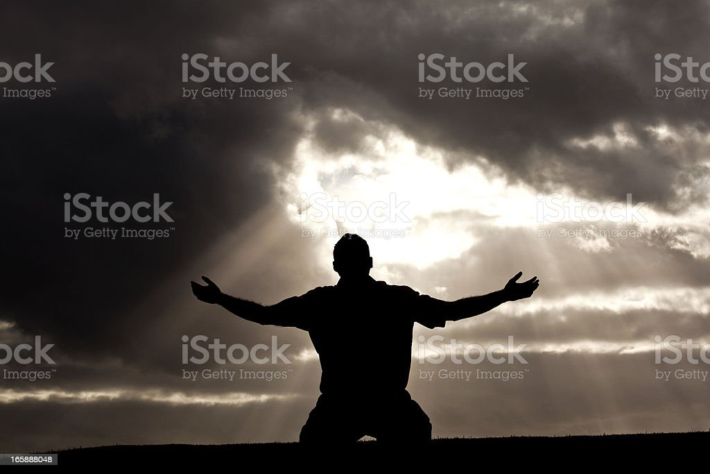 Silhouette of Unrecognizable Man in Worship Silhouette stock photo