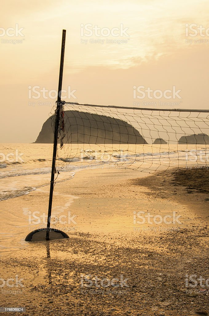 Silhouette of volleyball net on a beach at sunrise. royalty-free stock photo