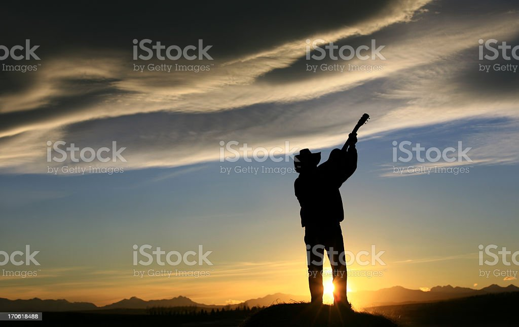 Silhouette of Western Country Music Guitar Player at Sunset stock photo