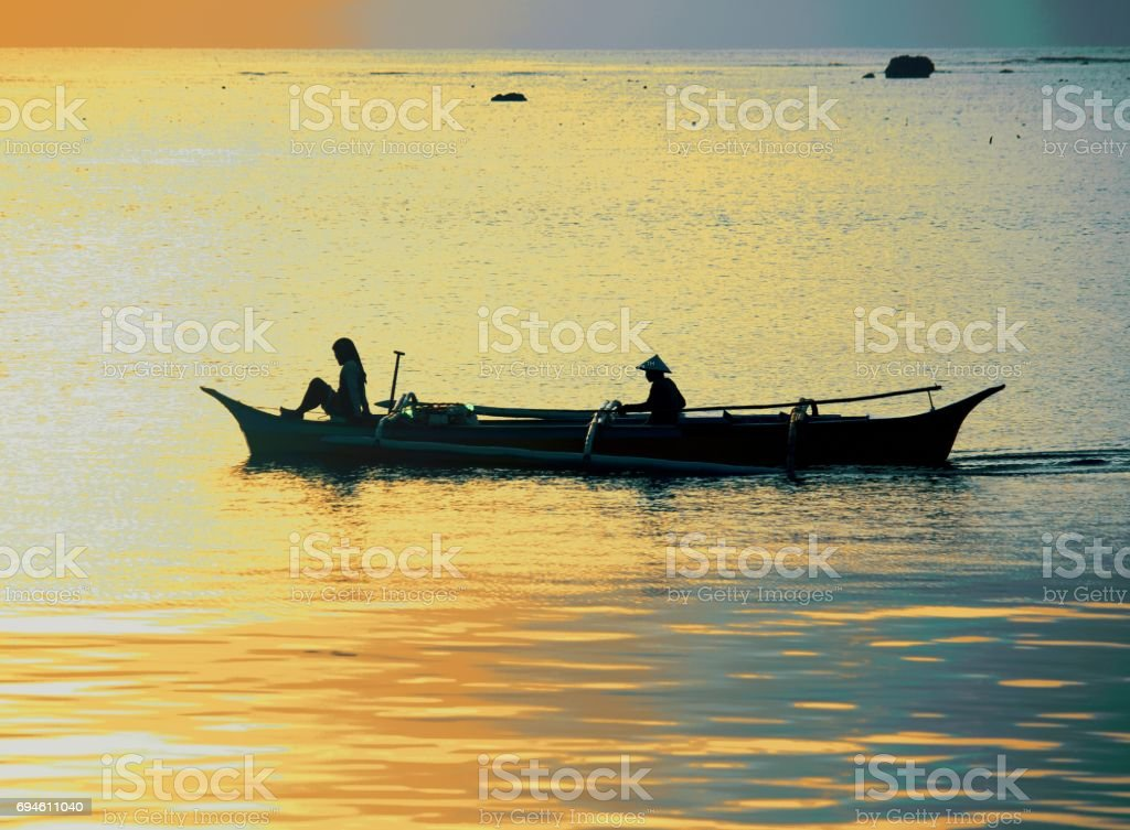 Silhouette of woman and boat man in boat at sunrise stock photo