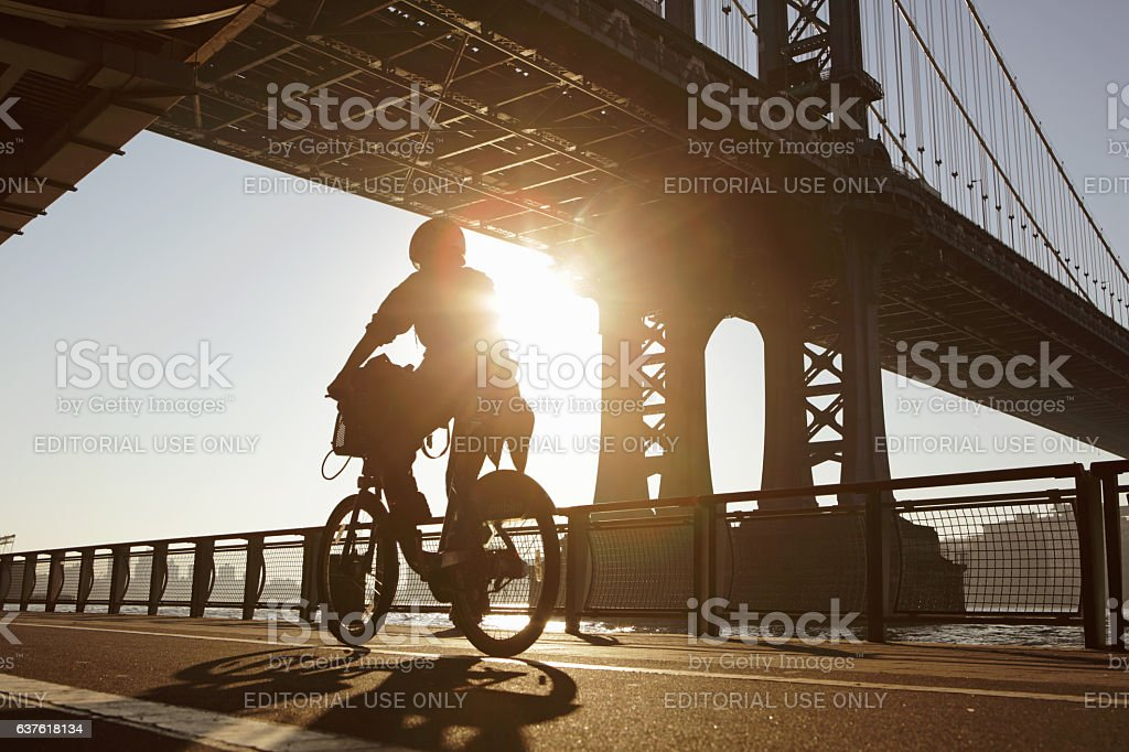 Silhouette of woman cycling along the East River Manhattan Bridge stock photo