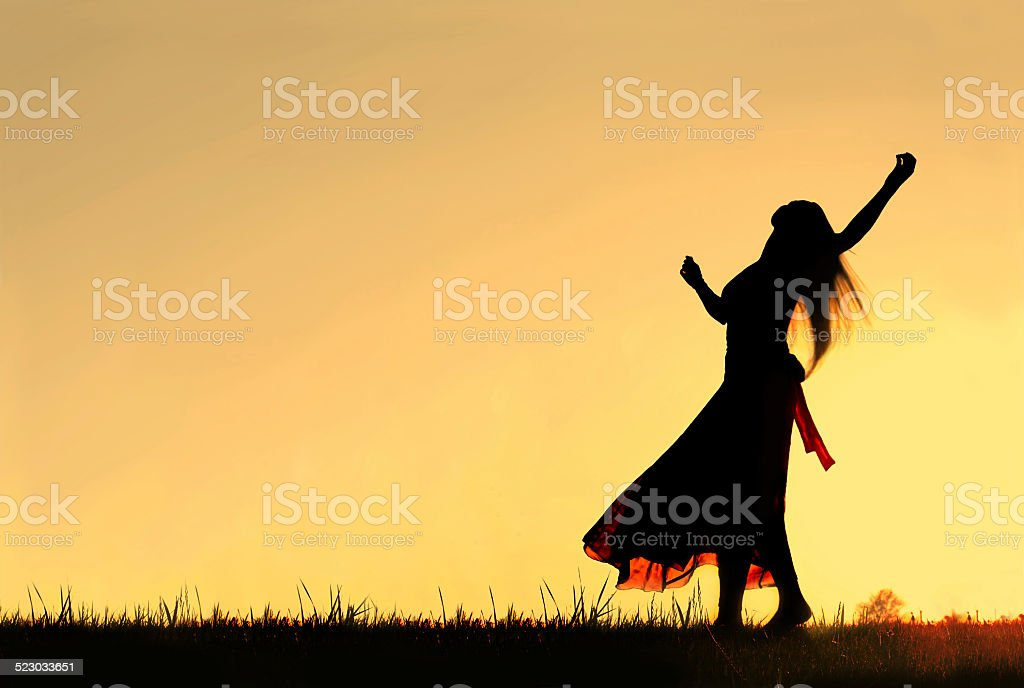 Silhouette of Woman dancing and Rejoicing to God at Sunset stock photo