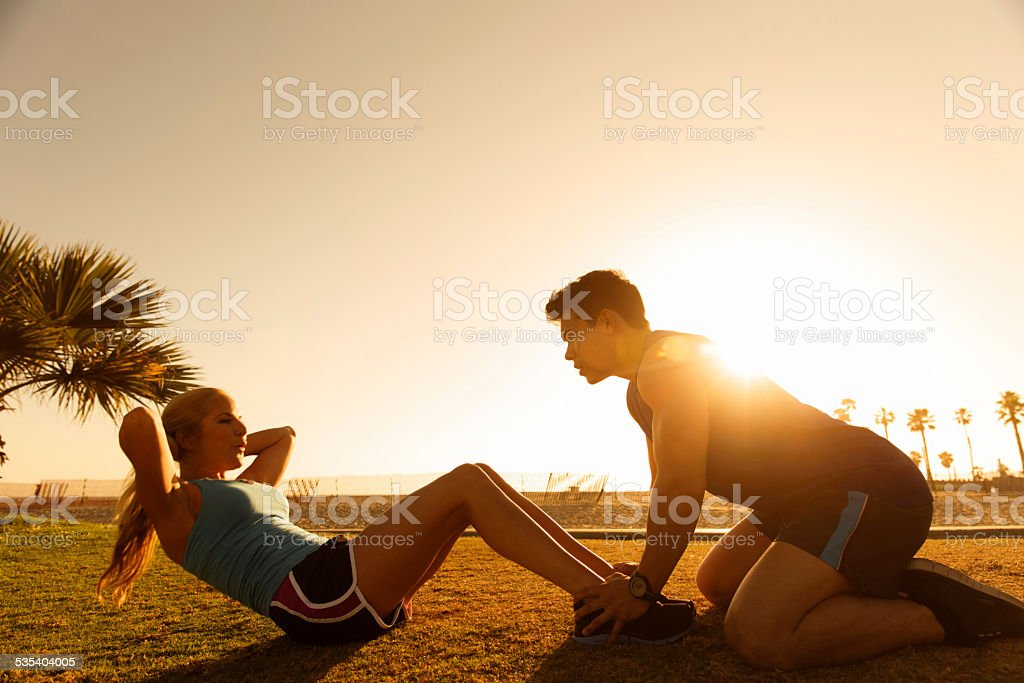 Silhouette of Woman doing Situps with Man at Venice Beach stock photo